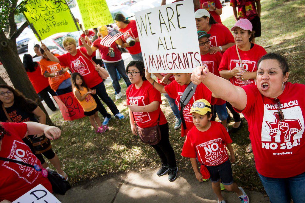 """Zoila Chaver (right) shouts with opponents of the SB4 law, Texas' """"sanctuary city"""" legislation, as they rally outside the  offices of State Rep. Matt Rinaldi on Wednesday, May 31, 2017, in Farmers Branch, Texas."""