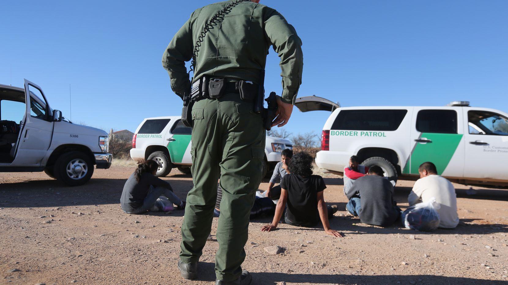 Un agente de la Patrulla Fronteriza vigila a un grupo de inmigrantes detenidos en la zona de Walker Canyon, al sur de Arizona.