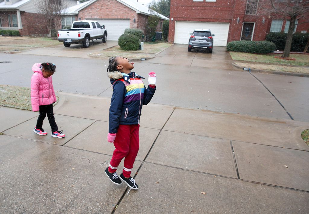 Six-year-old Dasiya Small, left and her sister 7-year-old Damyri Small try to catch snowflakes on their tongues in McKinney, Texas on Saturday, Jan. 11, 2020. (Brian Elledge/The Dallas Morning News via AP)