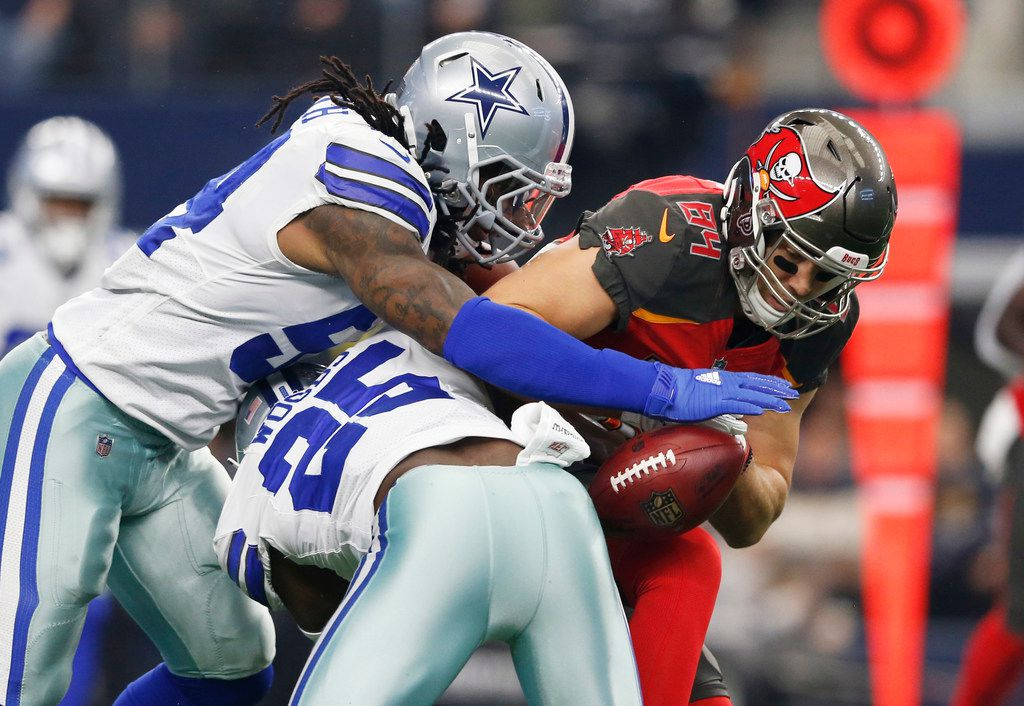Dallas Cowboys middle linebacker Jaylon Smith (54) and Dallas Cowboys free safety Xavier Woods (25) force Tampa Bay Buccaneers tight end Cameron Brate (84) to drop a pass during the first quarter of play at AT&T Stadium in Arlington on Sunday, December 23, 2018. (Vernon Bryant/The Dallas Morning News)