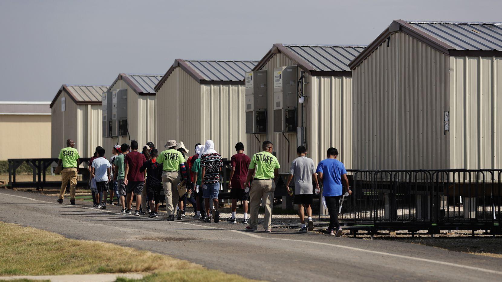 En esta fotografía del 9 de julio de 2019, unos miembros del personal escoltan a unos menores a una clase en un centro de detención para niños migrantes del gobierno de Estados Unidos en Carrizo Springs, Texas.