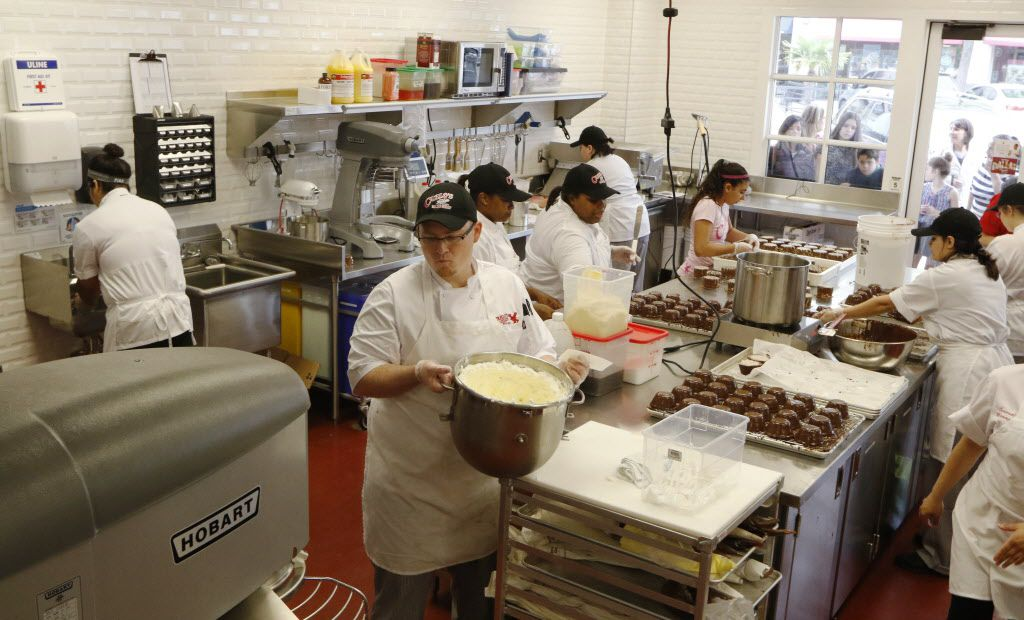 David Zimmerman, foreground, prepares white mousse at Carlo's Bakery on Friday,.