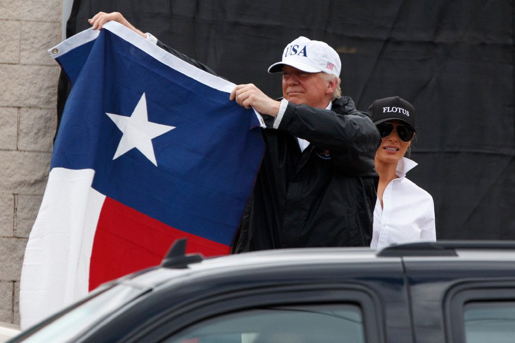 President Donald Trump, accompanied by first lady Melania Trump, holds up a Texas flag after speaking with supporters outside Firehouse 5 in Corpus Christi, Texas, uesday, Aug. 29, 2017, , where he received a briefing on Harvey relief efforts. (AP Photo/Evan Vucci)