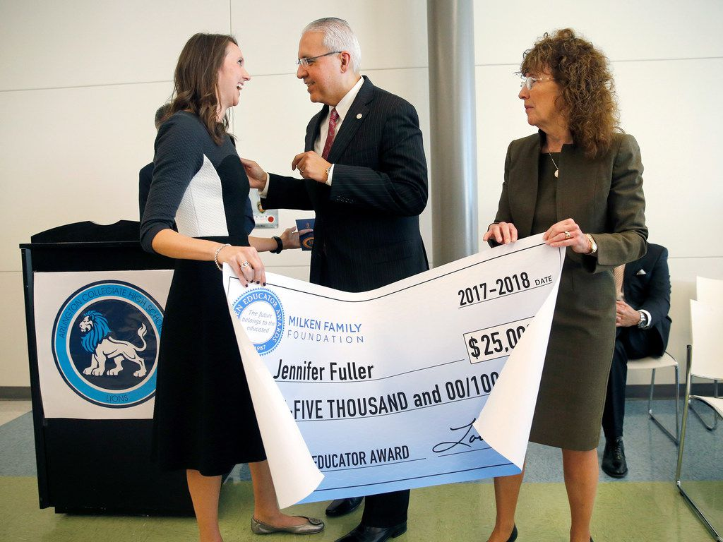 Arlington Collegiate High School teacher Jennifer Fuller (left) is congratulated by Arlington ISD Superintendent Dr. Marcelo Cavazos (center) on receiving the coveted Milken Educator Award, one of two in the state of Texas, during an assembly at the school in Arlington, Texas, Wednesday, October 18, 2017. The award came with a $25,000 check. Milken senior vice president Dr. Jane Foley (right) made the announcement. Forty five educators across the country received the award this year. (Tom Fox/The Dallas Morning News)