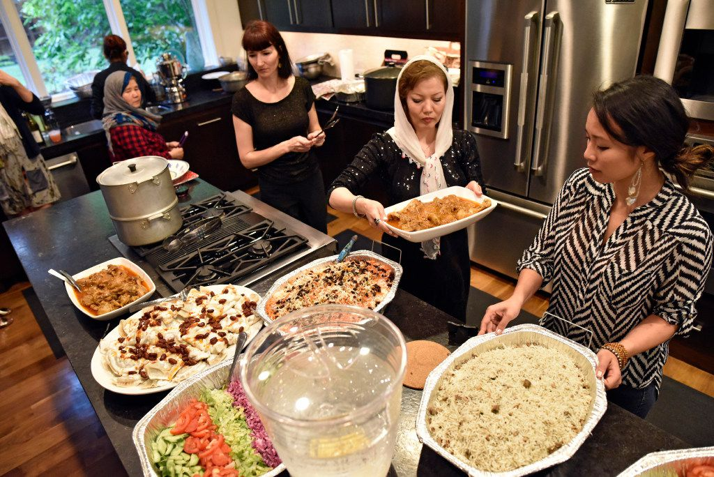 Olga Pope, left, Jamileh Jafari and Kim Simithraaratchy display food for an Afghan style dinner for the Sunday Supper Series in Dallas.