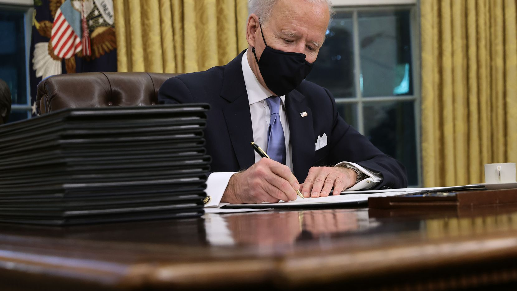 President Joe Biden signs executive orders at the Resolute Desk in the Oval Office just hours after his inauguration on January 20, 2021.