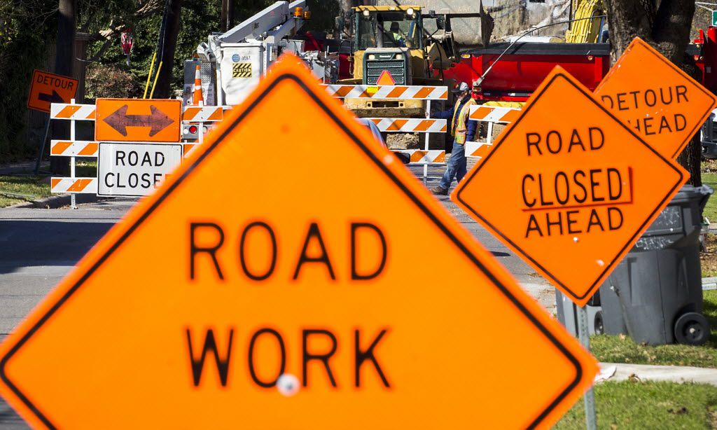 Signs point the way to a detour as crews work on street construction.