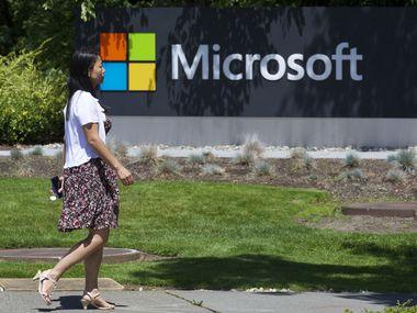 A pedestrian walks a sign on Microsoft Headquarters campus July 17, 2014 in Redmond, Wash. (Stephen Brashear/Getty Images/TNS)