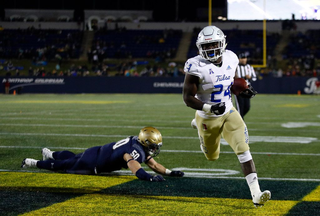 Tulsa running back Corey Taylor II scores a touchdown in front of Navy linebacker Diego Fagot in the second half of an NCAA college football game, Saturday, Nov. 17, 2018, in Annapolis, Md. (AP Photo/Patrick Semansky)