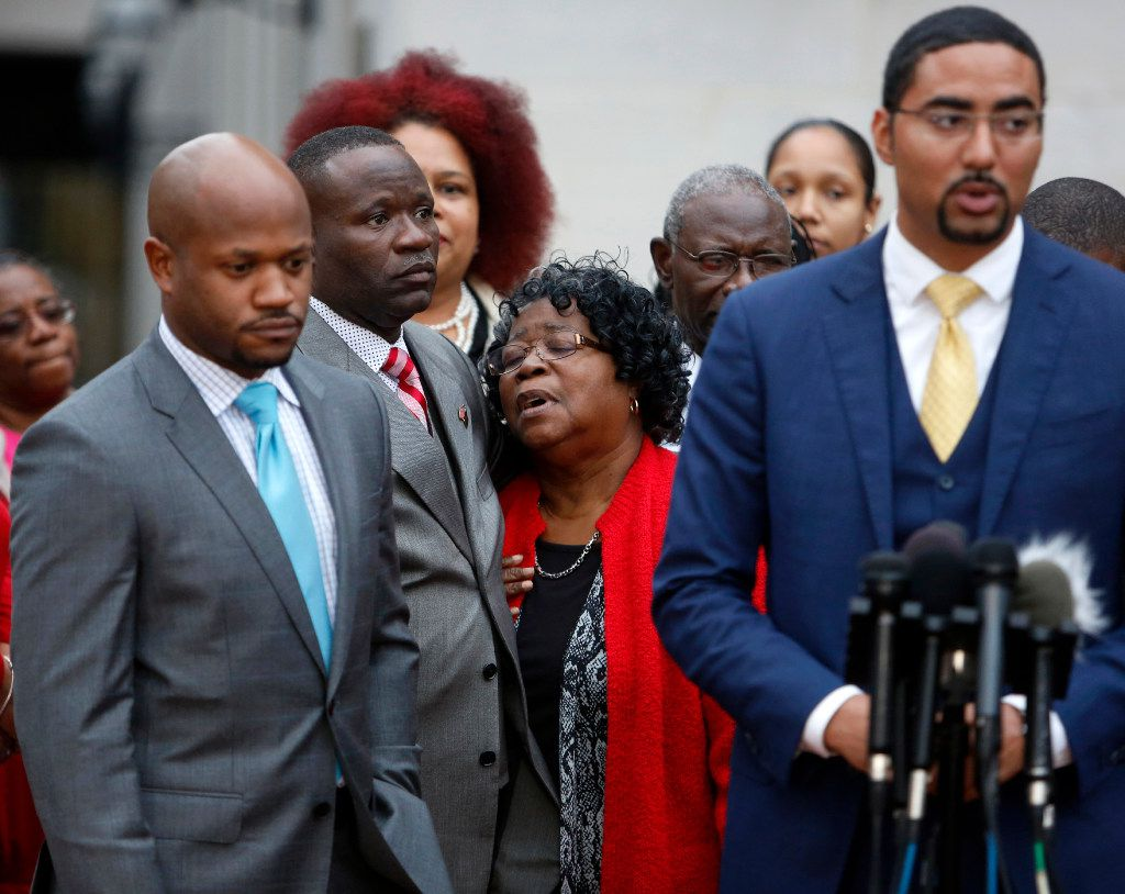 Judy Scott, center, Walter Scott's mother, is comforted by her son Rodney Scott, as the family attorneys, Chris Stewart, left, and Justin Bamberg, right, hold a press conference after the mistrial was declared for the Michael Slager trial Monday Dec. 5, 2016, in Charleston, S.C. Former patrolman, Slager, is charged with murder in the shooting death of Walter Scott last year. (AP Photo/Mic Smith)