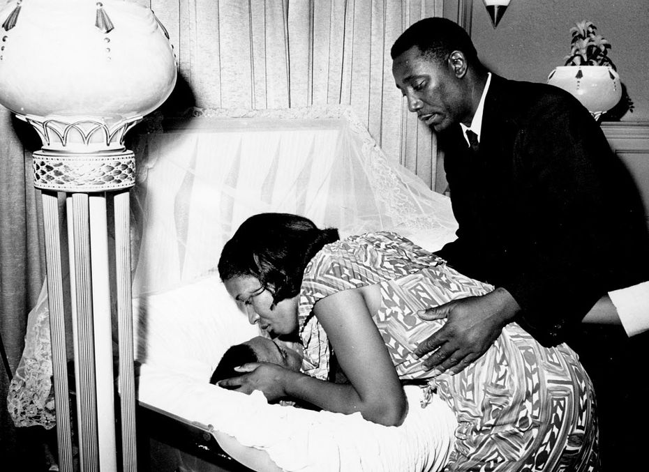 Myrlie Evers, the widow of civil rights activist Medgar Evers, leans down to kiss her late husband's forehead before the casket was opened for public viewing in the summer of 1963 at a funeral home in Jackson, Miss.