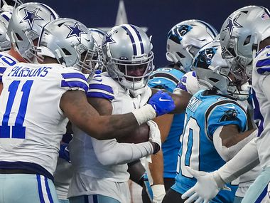 Dallas Cowboys cornerback Trevon Diggs (7) is mobbed by teammates, including with linebacker Micah Parsons (11), after intercepting a pass by Carolina Panthers quarterback Sam Darnold, the first of two interceptions for Diggs, during the third quarter of an NFL football game at AT&T Stadium on Sunday, Oct. 3, 2021, in Arlington.