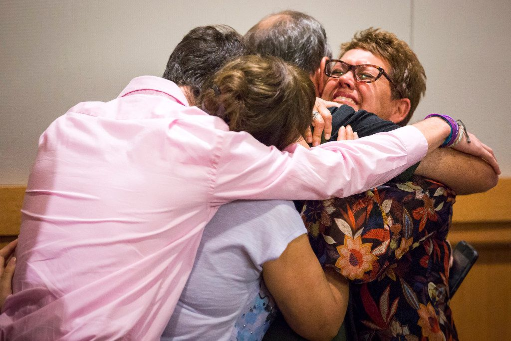 Christina Morris' mother, Jonni McElroy (facing), hugs family members after Arochi's guilt is announced. (Smiley N. Pool/Staff Photographer)