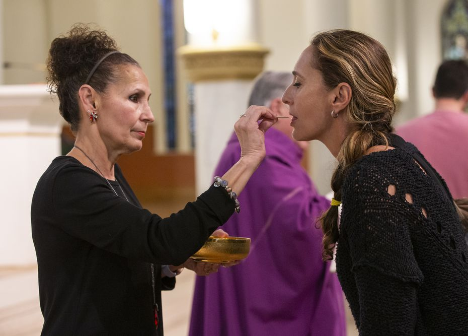 Gloria Figueroa (left) gives communion to a member of the Cathedral Shrine of the Virgin of Guadalupe congregation on March 13, 2020 in Dallas. Until canceling all services, the diocese had left it up to parishioners to decide whether they wanted to receive the host by mouth.