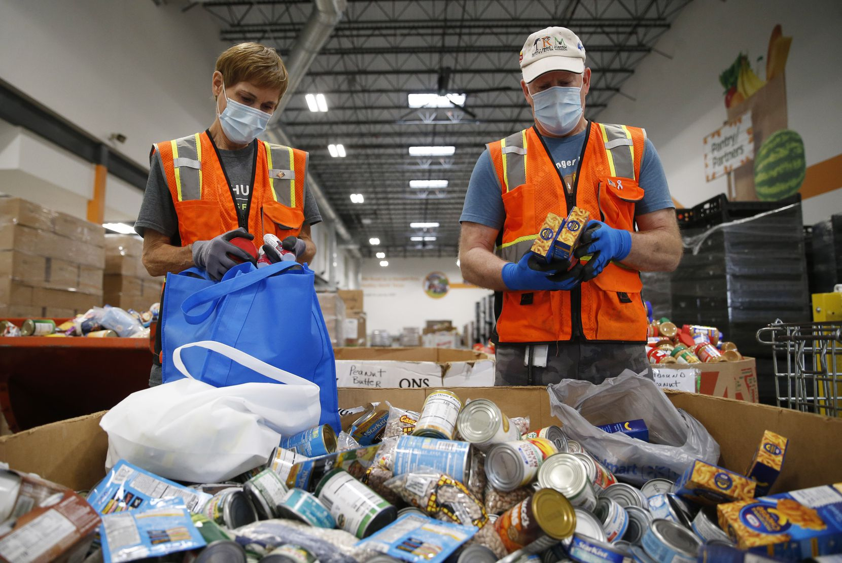 Volunteers Jill Mendenhall and her husband Max Chesser of Frisco work on sorting and checking the dates of food donations at North Texas Food Bank on Friday, November 20, 2020 in Plano, Texas. Mendenhall and Chesser started volunteering at North Texas Food Bank after they retired from Frito-Lay almost three years ago. After COVID-19 hit the U.S. in March, they made a decision to continue to volunteer, even though most of the fellow volunteers decided to stay home.
