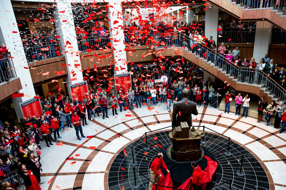 Employees popped confetti as Johnathan Dagerath (left) and Michael Fountas unveiled the James Cash Penney statue in the northside atrium at J.C. Penney headquarters in Plano on March 1, 2019. The company had downsized, so it moved the statue from its original location in the main atrium.