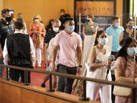 Vuong To, 21, center, wearing a face mask, walks into the Music Hall at Fair Park with his family to see a dress rehearsal of 'Wicked,' hosted by Dallas Summer Musicals, on Aug. 1 in Dallas.
