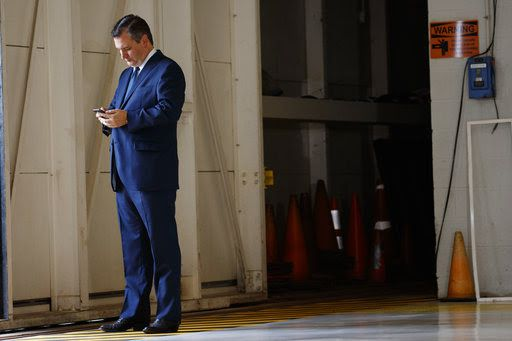 Sen. Ted Cruz, R-Texas, looks at his cell phone as he waits for the arrival of President Donald Trump at Coast Guard Air Station Houston, Thursday, May 31, 2018. (AP Photo/Evan Vucci)