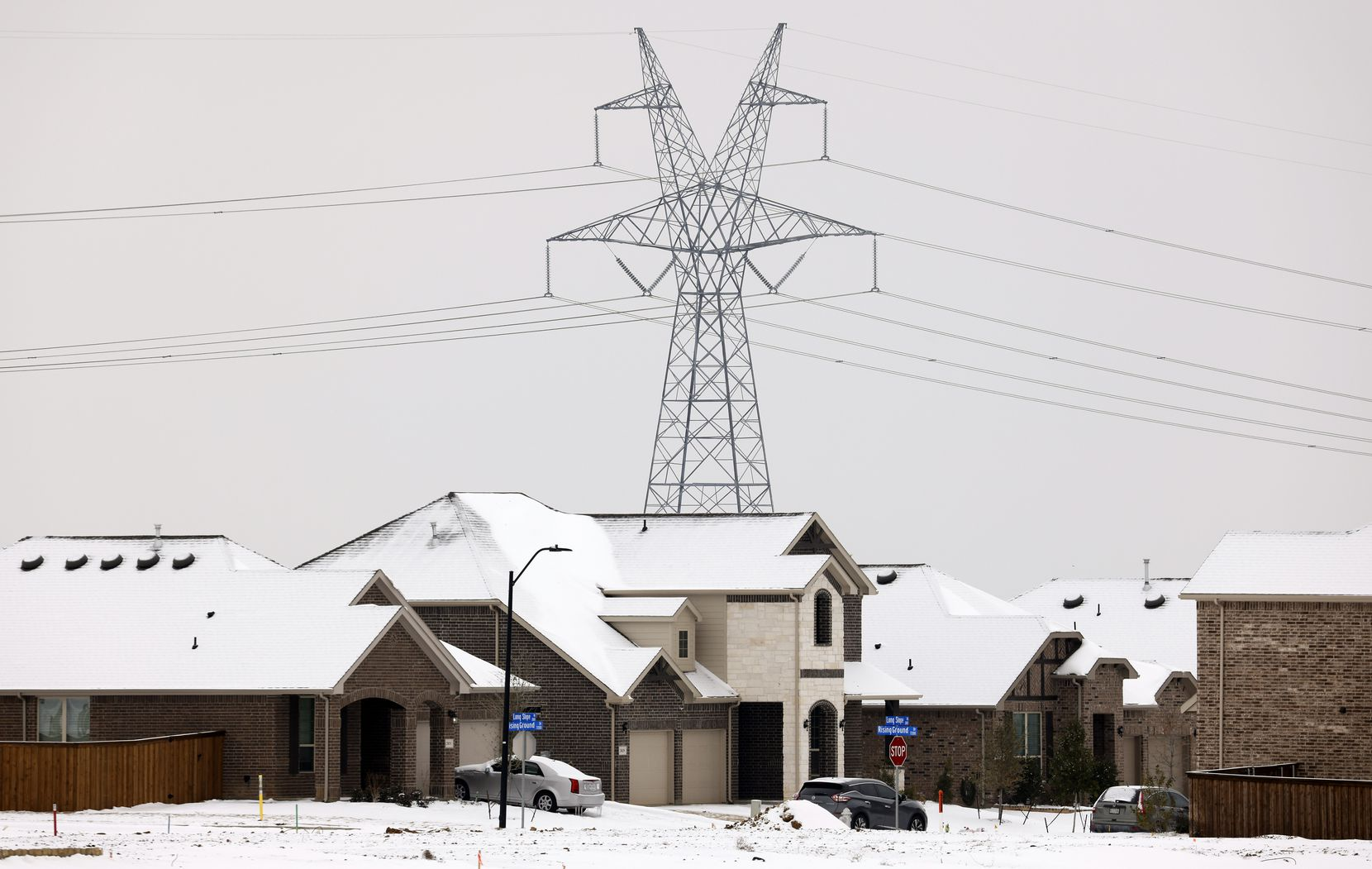 Large electrical transmission lines are seen in a new housing development in South Arlington on February 17, 2021, as rolling power outages disrupted service following a snow storm and deep freeze.