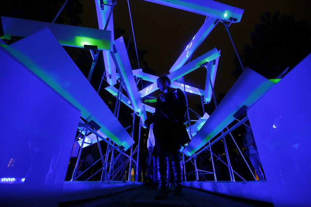 People walk through 'Data Flow', a blacklight sculpture by artists Erick Glissman, Scott Horn, and Nicole Cullum Horn which was installed in the middle of Flora St. for Aurora 2013 in the Dallas Arts District, Friday, October 18, 2013.