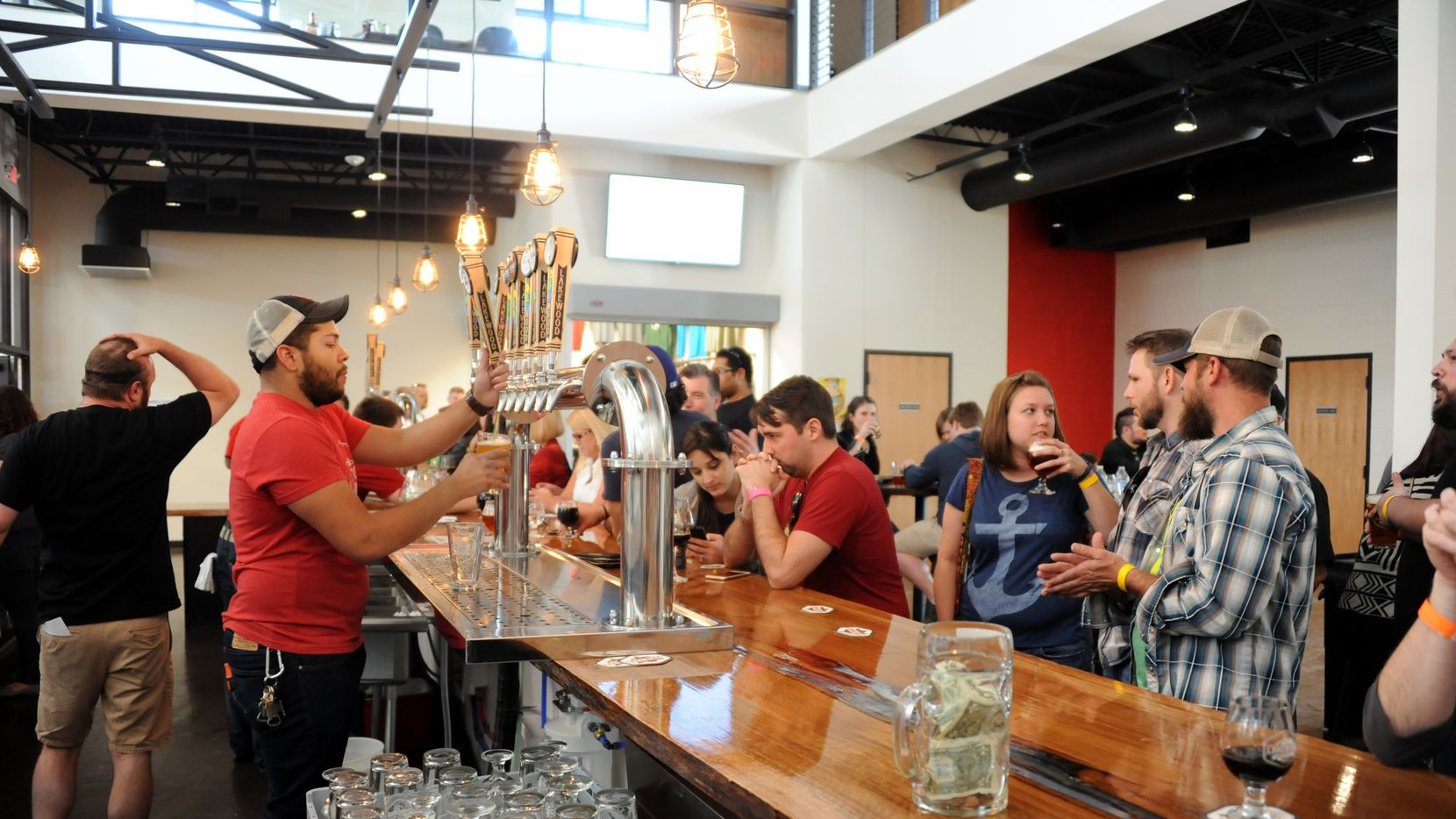 Bartender Quin Tinling serves a cold brew at Lakewood Brewing Company's  Taproom grand opening in April.