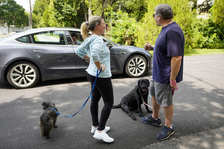 Michael Hoffman gave a thumbs up to his neighbors, who stopped to ask how he and wife Jackie were doing, while walking their dogs, Ozzie (left) and Lexi, near their home on Sept. 13, 2020.