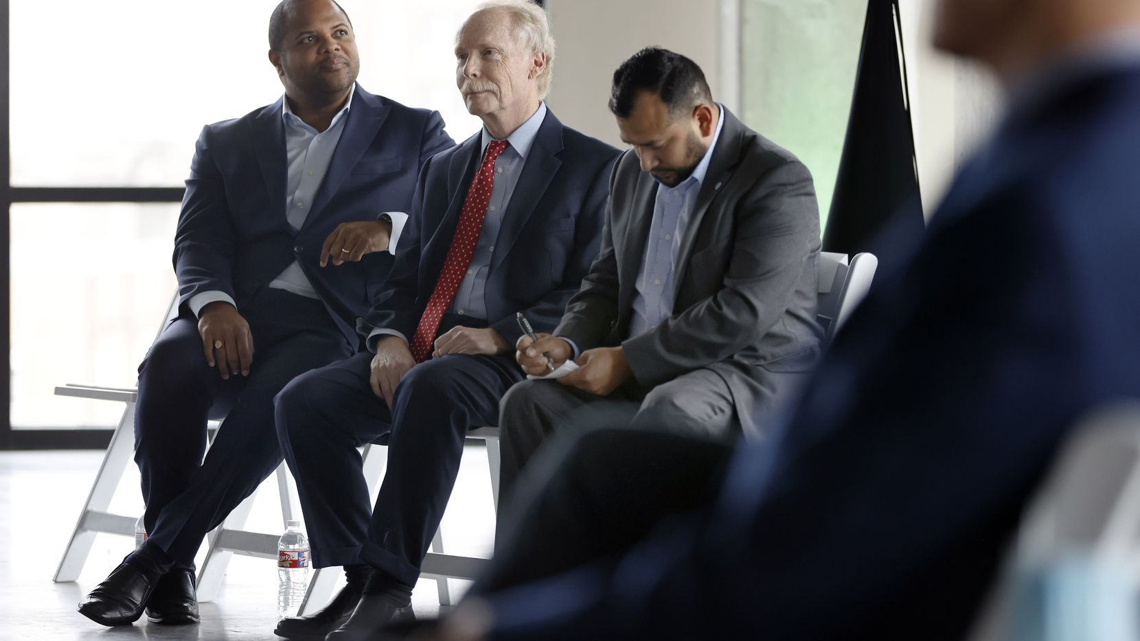 Dallas City Councilman Paul Ridley, center, sits with Mayor Eric Johnson, left, and City Councilman Jesse Moreno, right, during a ceremonial groundbreaking of Harwood Park in September 2021 in downtown Dallas.  (Tom Fox/The Dallas Morning News)