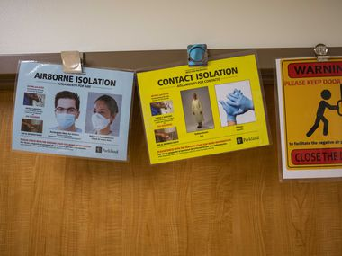 Each patient room in the areas of Parkland Memorial Hospital devoted to COVID-19 cases displays a variety of warnings and protocols for caregivers and other staff.