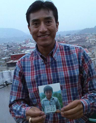The adult Carlos holds up a photograph of himself as a child in Guatemala.