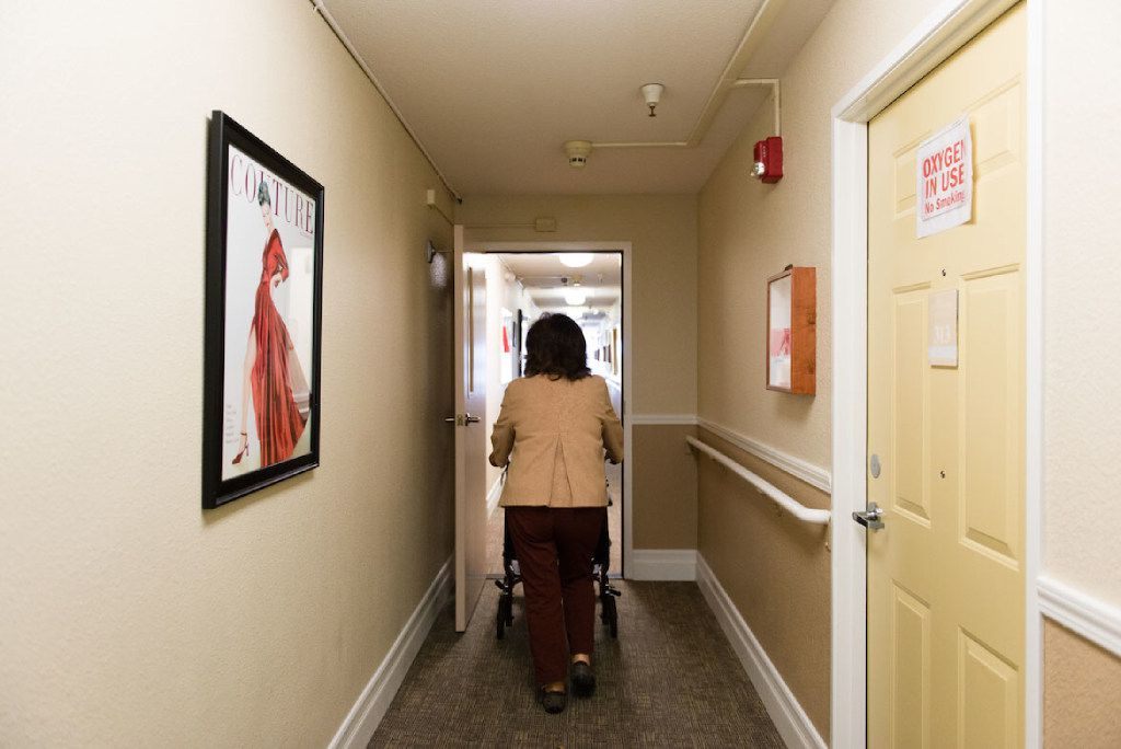 Barbara Marquez, 61, wheels her mother down the corridor of the Sagebrook Senior Living home on Friday, December 16, 2016 in Carmichael, Calif. (Heidi de Marco/KHN/TNS)