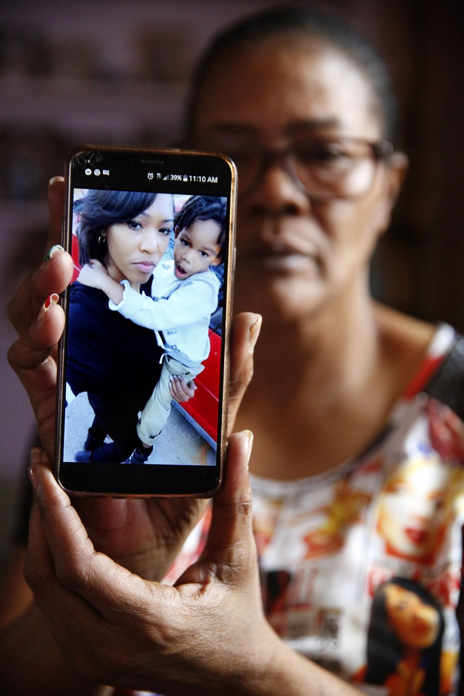 Tammy Kirk, mother of LaTiffiney Rodgers, who was fatally shot and her sons were the subject of an Amber Alert, is photographed in her Cedar Hill home. She is holding a photo on her phone of LaTiffiney and her oldest son, 7-year-old Jorden Rodgers.