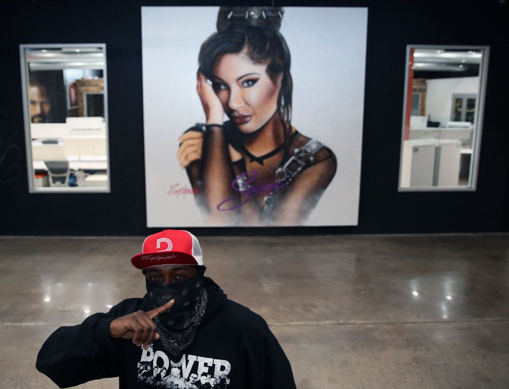 Artist Theo Ponchaveli in front of a Selena artwork. Ponchaveli, who normally covers his face while painting to protect from fumes, said people usually see him wearing a bandanna so he wears it in photographs. His first Selena mural was on his previous studio in Oak Cliff.
