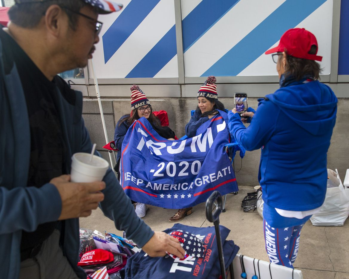 Lacey Green (center left) and her mother Tammy Gonzales (center right) from San Antonio, Texas, have their photo taken while they camp out in line in front of the American Airlines Center in Dallas on Wednesday, Oct. 16, 2019. President Donald Trump will host a rally at the center on Thursday evening.