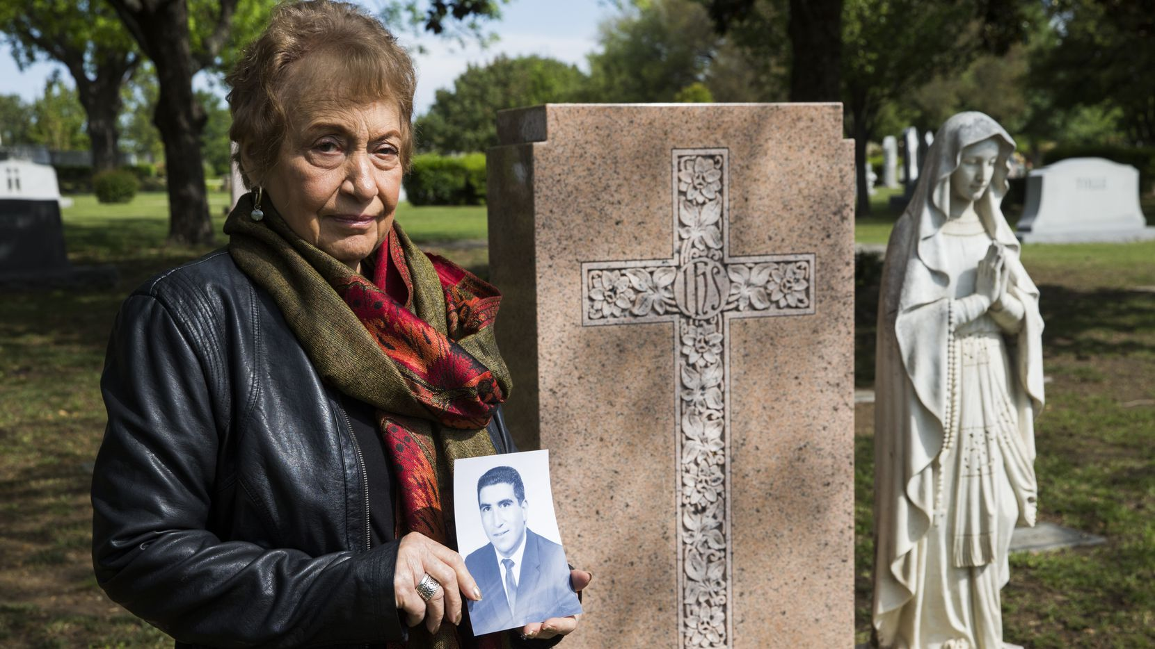 Lucy Campise holds a photo of her husband, Frank Campise, at Frank's grave on April 18, 2020, at Calvary Hill Cemetery in Dallas.