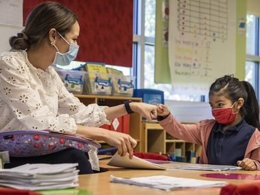 Kindergarten teacher Michelle Davis gives a fist bump to Angelique Luciano, 6, after administering a quick literacy diagnostic test to her at F.P. Caillet Elementary in Dallas on Wednesday, May 5, 2021. These bimonthly, quick diagnostic assessments give her the info she needs to plot out how to get her students on track amid the pandemic. (Lynda M. González/The Dallas Morning News)