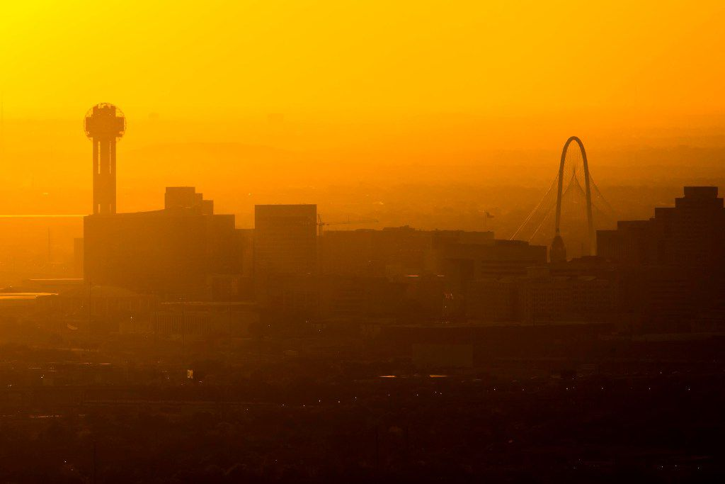 Sun setting behind the Downtown Dallas skyline and the Margaret Hunt Hill Bridge on Thursday, March 23, 2017, in Dallas, TX. (Smiley N. Pool/The Dallas Morning News)
