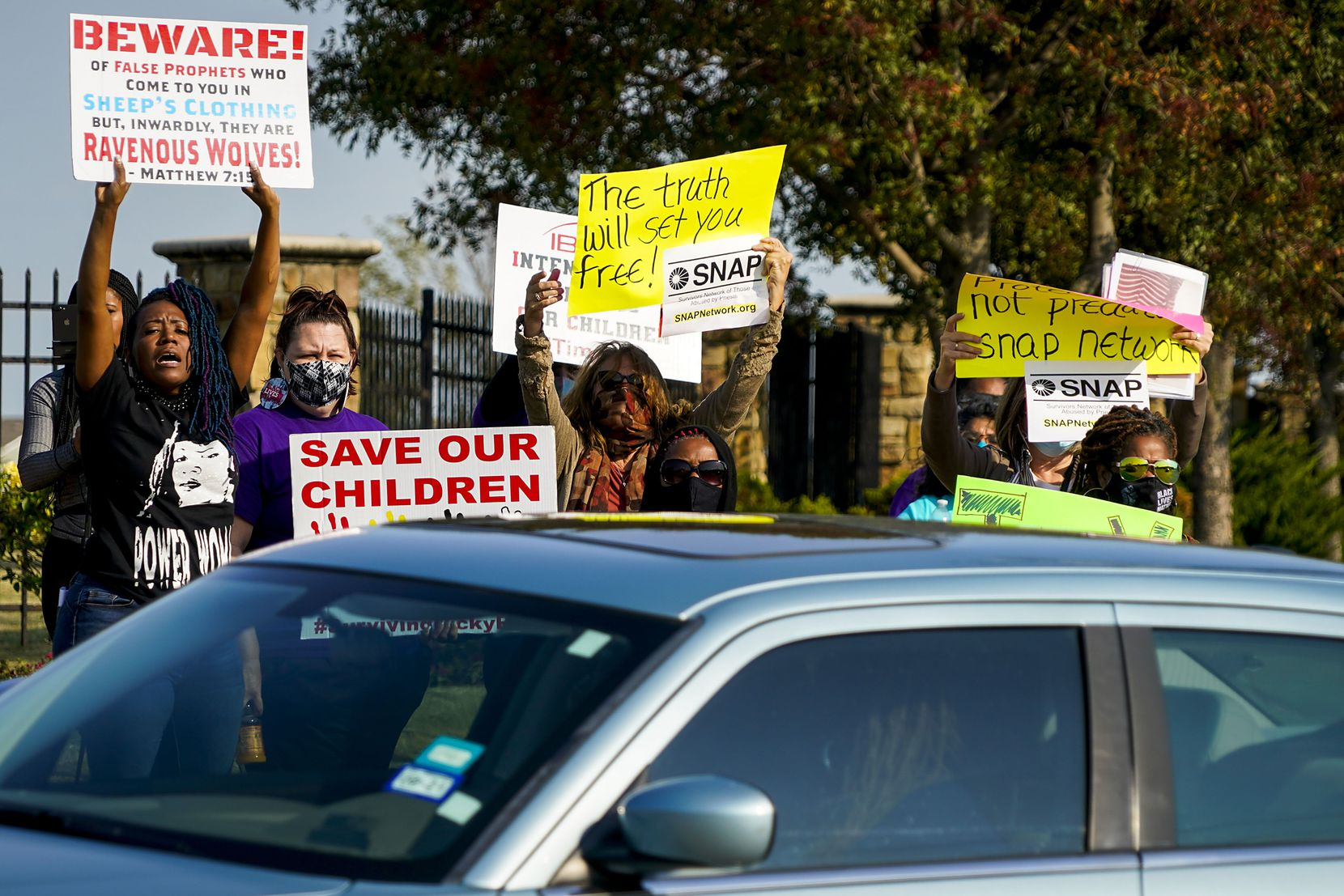 Demonstrators, including Donna Fields (left), yelled toward motorists entering the parking lot at Inspiring Body of Christ Church before services last Oct. 4.
