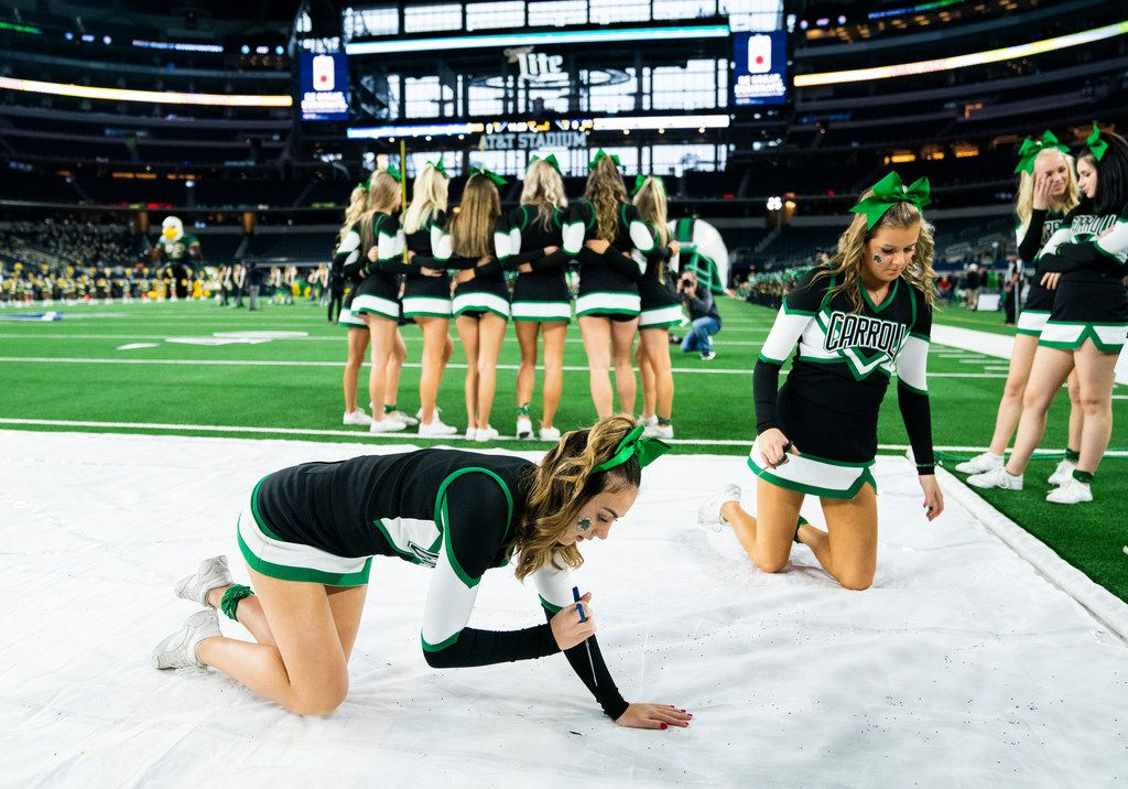 Southlake Carroll cheerleaders prepare a banner for the team to run through before a Class 6A Division I area-round high school football playoff game between Southlake Carroll and DeSoto on Friday, November 22, 2019 at AT&T Stadium in Arlington. (Ashley Landis/The Dallas Morning News)