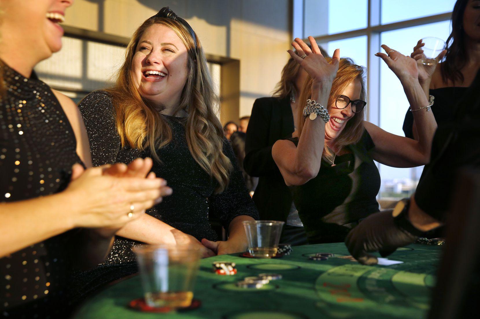 Monument Realty agents Kristi Drayovitch (center) and Brenda Sukenik (right) celebrate a winning blackjack hand at a casino night in August.