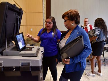 Laura Varela, left, a bilingual coordinator for Dallas County Elections, explains to Constancia Shaw how to scan her printed ballot during a demonstration of the new equipment for elections, Sept. 25, 2019 at City Hall in Mesquite.