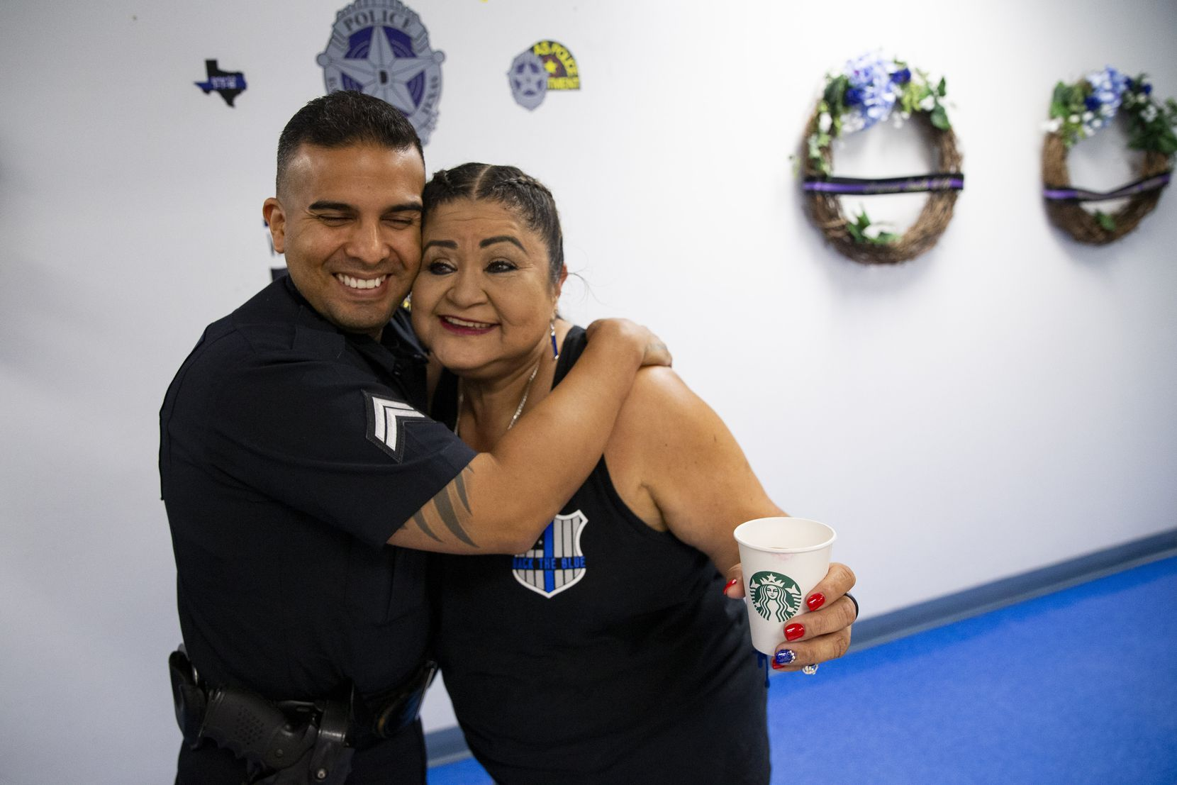 Valerie Zamarripa hugs Sr. Corporal Ruben Lozano on Friday, July 2, 2021, at the Dallas police Southwest Patrol division in Dallas. They are pictured in front of a wall honoring the five police officers who were killed when a gunman ambushed an evening of protests in downtown Dallas on July 7, 2016. Lozano worked with Zamarripa's son, Patrick Zamarripa, who was one of the five officers killed.