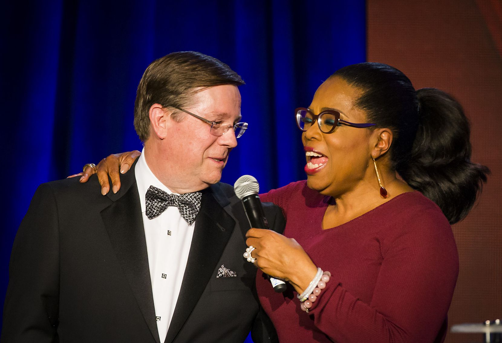 Oprah Winfrey puts her arm around Jim Lentz, chief executive officer of Toyota Motor North America, as takes the stage to pledge a donation during the Minnie's Food Pantry 10th anniversary gala at the Omni Frisco Hotel on Tuesday, April 3, 2018. During her speech, Winfrey challenged attendees to match her $250,000 donation to the organization, then a line formed and one-by-one donors took to the stage to make pledges.  By the end of the night, approximately $1.3 million had been raised.