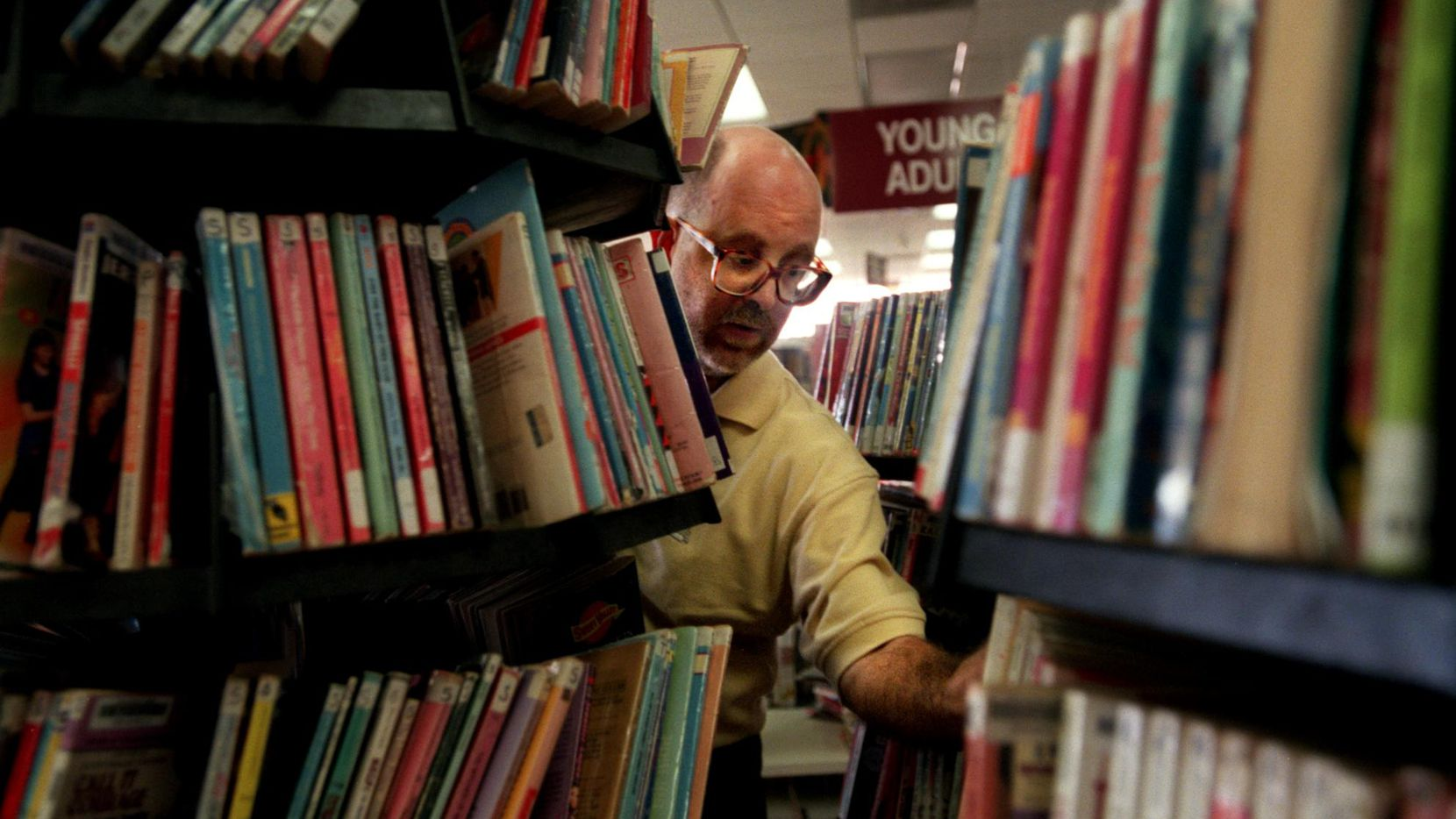 In this file photo, Charles David Smith, 39, puts books away at the North Oak Cliff Branch Library where he works as a page.