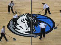 The Mavs logo at half court gets some TLC during a time out during the Orlando Magic vs. the Dallas Mavericks NBA basketball game at the American Airlines Center in Dallas on Tuesday, January 9, 2018.