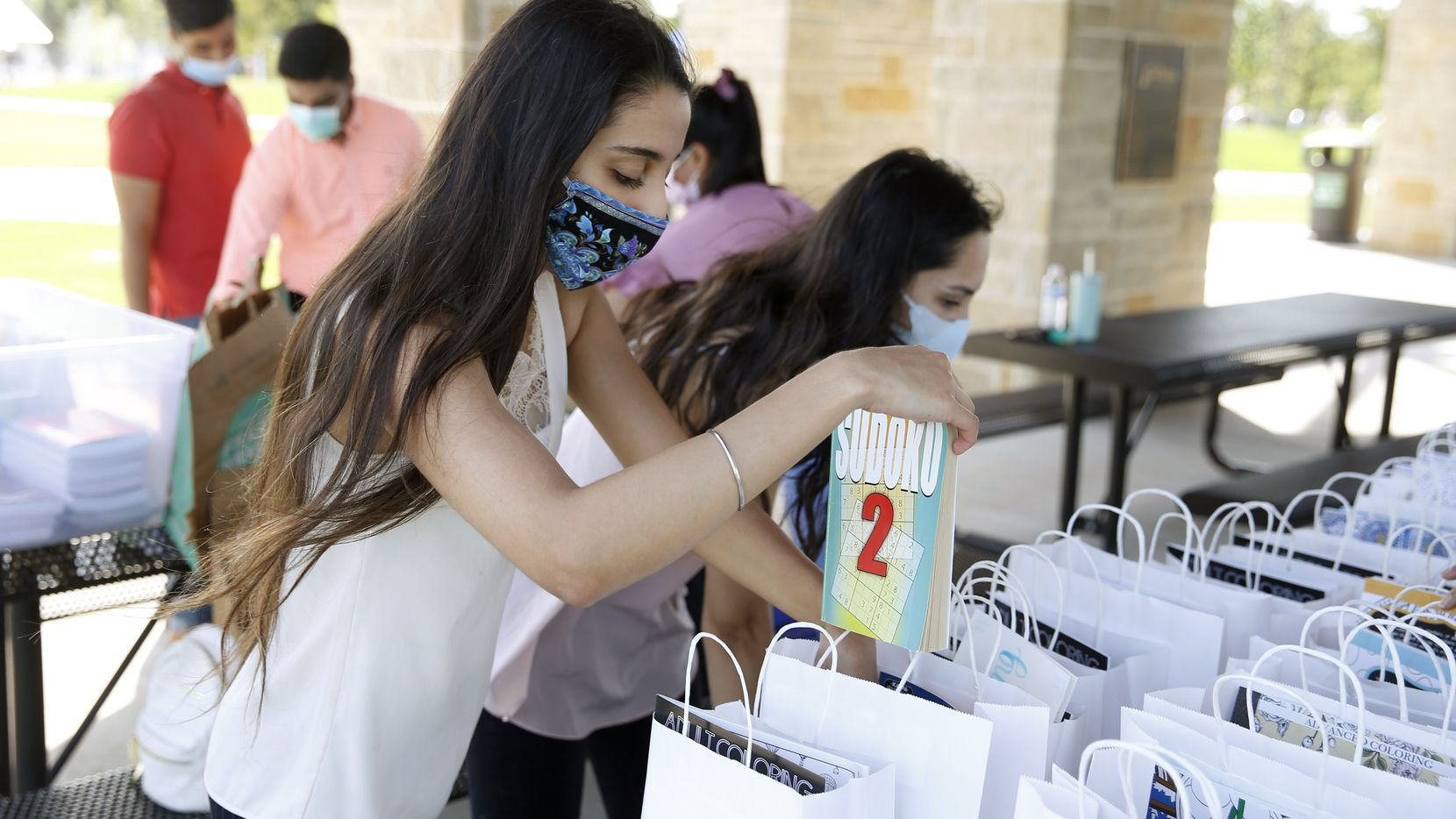 Kareena Chawla, a volunteer with COVID Check-In, works on making care packages for seniors living at Windhaven Meadows Park in Plano. The group also made 45 bags for delivery to Saddle Brook Memory Care Community in Frisco. (Vernon Bryant/The Dallas Morning News)