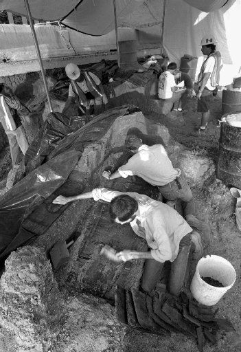 8/5/93--Historical Archaeologist James  Davidson, left, brushes some soil off the top of a coffin as Archaeologist asst. Randall Banks, center, scrapes dirt from  around the front of the coffin early Thursday morning at Freedman' s Cemetery. Davidson estimated the coffin to have been buried  between 1900 and 1908.