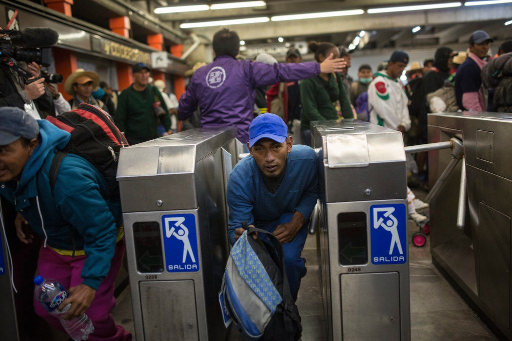 A Central American migrant bypasses a subway turnstile after leaving the temporary shelter at the Jesus Martinez stadium, in Mexico City, Friday, Nov. 9, 2018. About 500 Central American migrants headed out of Mexico City on Friday to embark on the longest and most dangerous leg of their journey to the U.S. border, while thousands more were waiting one day more at the stadium.