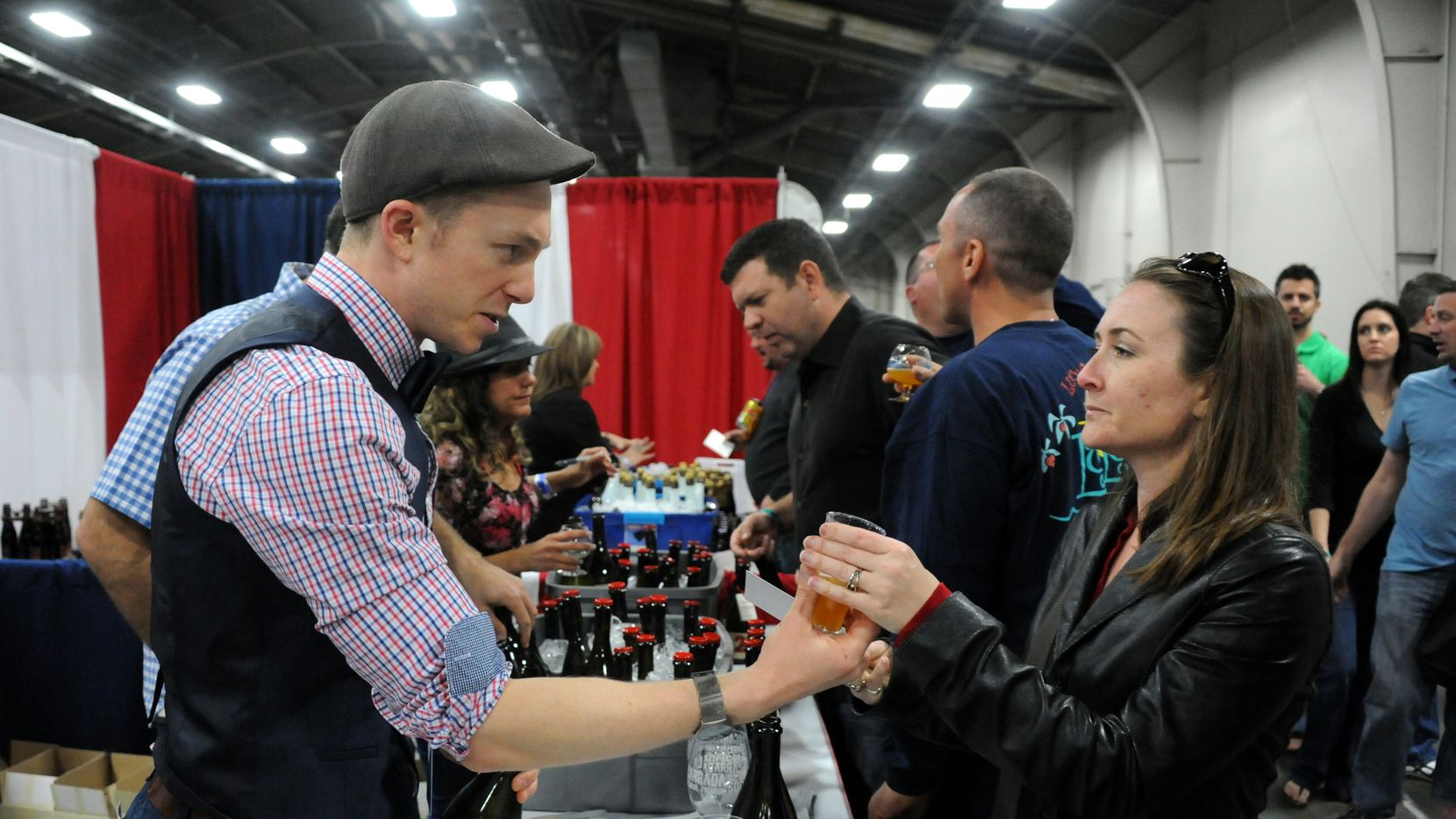 Austin Calr serves a La Socarrada beer to guest Carisa Armstrong at the Big Texas Beer Fest at Fair Park in Dallas, TX on April 5, 2014.