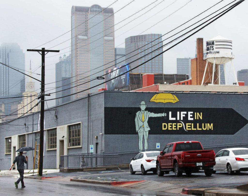 An appropriate sign on a Deep Ellum building is pictured with part of the downtown Dallas skyline in the background during a rainy day.