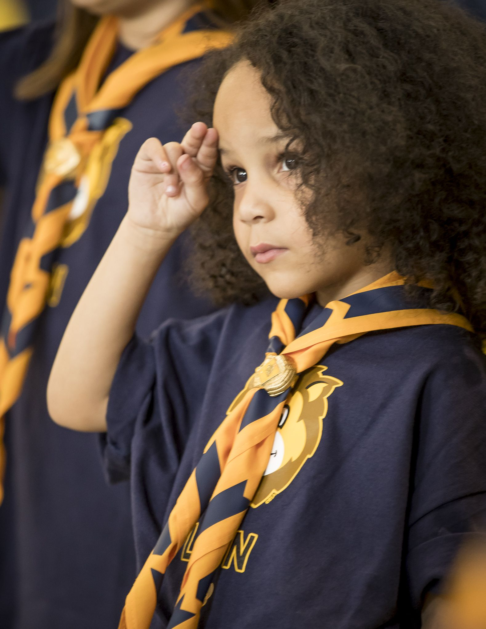 A young Cub Scout stands in uniform to salute with her fellow Scouts.